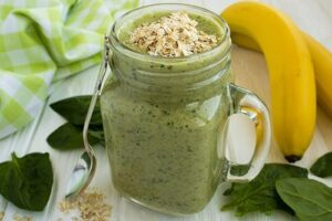 "Photograph of a green smoothie in a glass mug topped with oatmeal, from ""10 Easy Green Smoothies Kids Will Love"" at Green Smoothie Girl"