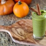 "photo of a green smoothie with two cinnamon sticks in it with pumpkins in the background from Green Smoothie Girls's ""green pumpkin smoothie"""