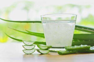 "Fresh aloe vera leaves and aloe vera juice in glass on wooden background, from ""12 Proven Health Benefits of Aloe Vera"" at Green Smoothie Girl."