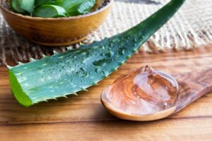 "Aloe vera gel on a wooden spoon with a whole aloe vera leaf in the background, from ""12 Proven Health Benefits of Aloe Vera"" at Green Smoothie Girl."