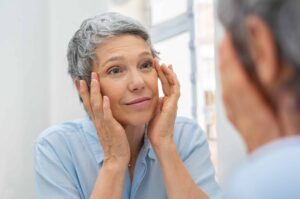 "Photograph of a middle-aged woman looking in the mirror and touching her wrinkles, from ""Health Benefits of Red Light Therapy: Legit or Hype?"""