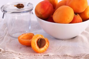 "Fresh apricots in a bowl, one apricot just halved, on natural linen cloth and white background, from ""Health Benefits of Sulfur, and Why You're Probably Deficient"" at Green Smoothie Girl."