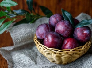 Photograph of a basket of plums on a burlap cloth, from