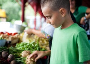 "Photograph of a pre-teen boy looking at vegetables at a farmers' market, from ""Healthiest Smoothie Recipes for Each Season of the Year"" at Green Smoothie Girl."