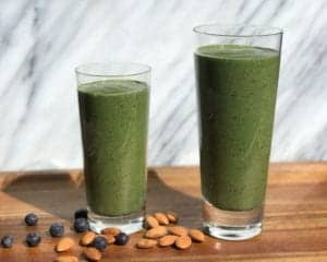 "Photo of two green smoothies in a big and small glass with blueberries and almonds scattered on a wood surface with marble in the background from ""Super Hulk Green Smoothie"" recipe by Green Smoothie Girl"