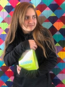 "Photograph of a teenage girl holding a box of Blendbars against a multi-colored background, from ""Why Most Nutrition Bars are Garbage -- and What to Pack in Your Purse Instead"" at Green Smoothie Girl"