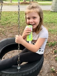 "Photograph of a young girl on a tire swing eating a Blendbar nutrition bar, from ""Why Most Nutrition Bars are Garbage -- and What to Pack in Your Purse Instead"" at Green Smoothie Girl"