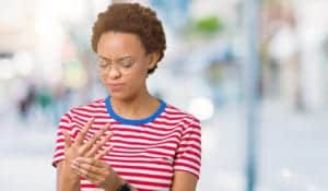 "Photo of African American woman experiencing joint pain in her fingers, from ""These Anti Inflammatory Smoothie Recipes Target Joint Pain And More"" at Green Smoothie Girl."