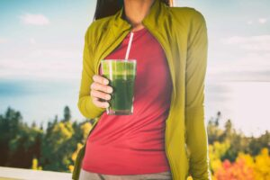 "Photograph of a person drinking a green smoothie, from ""Why You Should Chew Your Green Smoothies"" at Green Smoothie Girl."