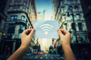 Photo of a person holding a paper with the Wi-Fi symbol on it, from