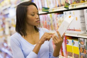 Photograph of a woman reading a box label at the grocery store, from