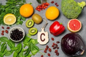 """Photograph of Vitamin-C-rich fruits and vegetables on a gray background, from """"Vitamin C: Ascorbic Acid Supplements Can Hurt Your Health"""" at Green Smoothie Girl."""