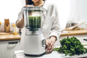 Photo of woman using a blender, from