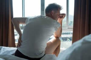 "Photograph of a man in a white t-shirt sitting on the edge of his bed, grasping his back in obvious pain, from ""Vitamin C: Ascorbic Acid Supplements Can Hurt Your Health"" at Green Smoothie Girl."