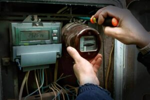 Photo of an old analog meter being uninstalled in favor of a smart meter from