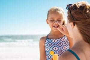 "Photo of woman putting sunscreen on child from ""Sun Exposure, Sunburn Prevention, & 5 Effective Natural Sunburn Treatments"" at Green Smoothie Girl."