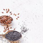 "Image of a spoonful of chia seed and a spoonful of flax seed on a white countertop, from ""Chia Seed vs. Flax Seed: Similarities, Differences, and When to Use Each"" at GreenSmoothieGirl"