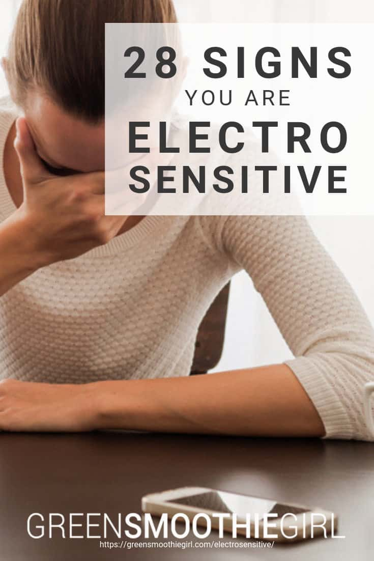 "Photo of woman holding her forehead in her hand and cellphone on the table with post's title text overlaid from ""28 Signs That You Are Electrosensitive"" by Green Smoothie Girl"