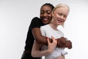 Photo of African American friend hugging white friend from