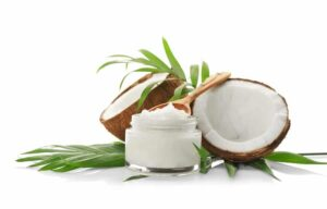 Picture of open coconut and jar of coconut oil with wooden spoon from