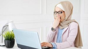 Photo of Muslim woman yawning at desk from