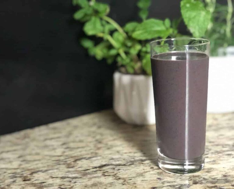 "Photo of purple smoothie in tall glass with two plants in white pots behind it from ""Morning Berry Smoothie"" recipe by GreenSmoothieGirl"