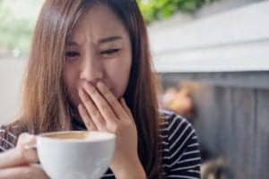 Photo of Asian woman holding coffee cup with bad look on face from