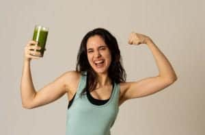 Photo of Latina woman flexing with green smoothie in one hand