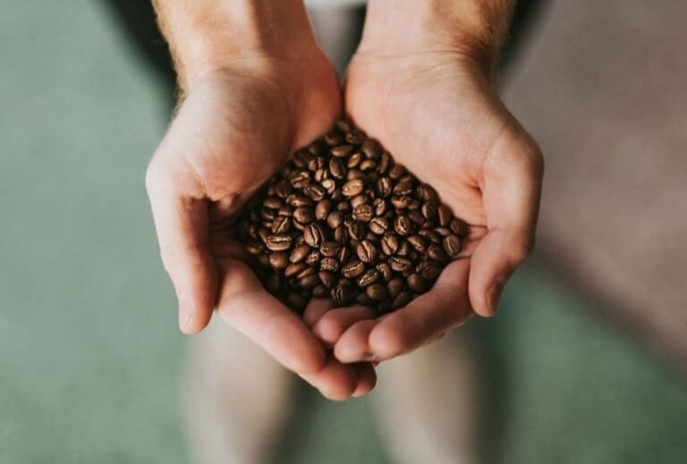 "Photo of hands offering coffee beans from ""3 Ways to Make Your Coffee Healthier"" by Green Smoothie Girl"