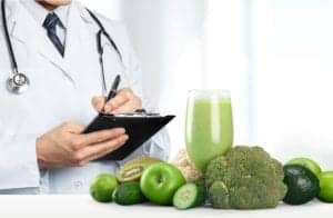 A doctor with a prescription pad out and a green smoothie with surrounding vegetables and fruits in front of him from