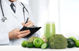 "A doctor with a prescription pad out and a green smoothie with surrounding vegetables and fruits in front of him from ""How To Make A Green Smoothie: The Foolproof Guide"" by Green Smoothie Girl"