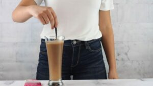 "Photo of woman stirring GreenSmoothieGirl chocolate plant protein powder into glass of water from ""Modified Fasting 101: The Ultimate Beginner's Guide"" by Green Smoothie Girl"