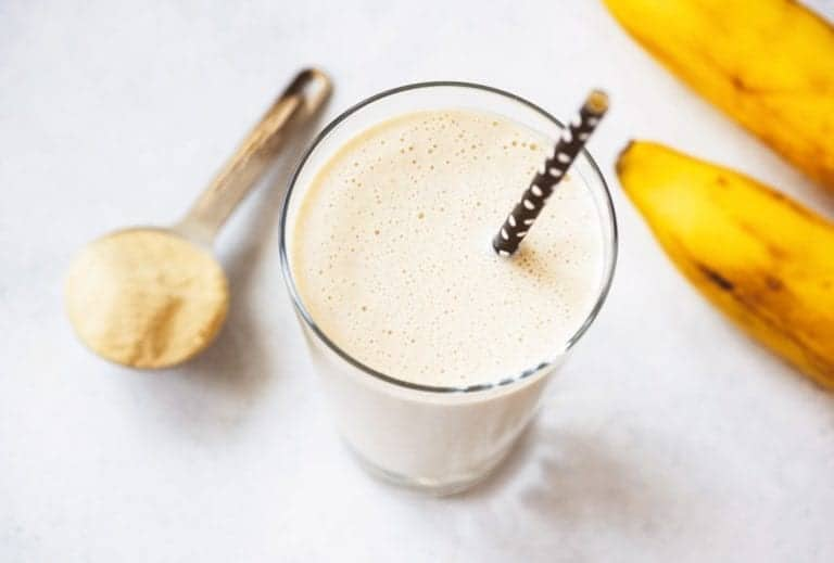 "Photo of vanilla smoothie with straw and scoop of protein from ""Modified Fasting 101: The Ultimate Beginner's Guide"" by Green Smoothie Girl"