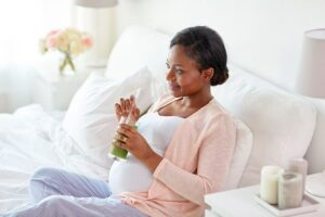 Photo of pregnant black woman laying in bed drinking a green smoothie from