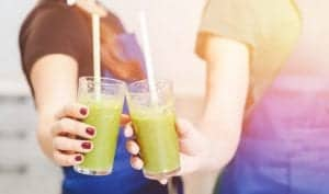 Photo of two girls clinking green smoothie glasses with straws from