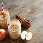 "Photo of apple cinnamon smoothie with apples and cinnamon sticks in background from ""Warm Apple Smoothie"" recipe by Green Smoothie Girl"