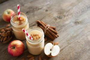 Photo of apple cinnamon smoothie with apples and cinnamon sticks in background from