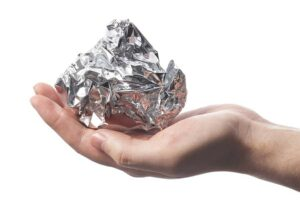 Photo of hand holding ball of aluminum foil from
