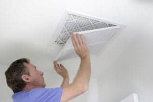 Photo of man shutting HVAC grill after replacing air filter in home from