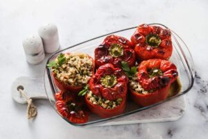 Photo of baked stuffed peppers in a glass baking pan from
