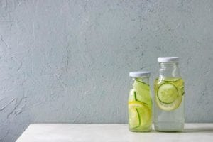 "Photo of two clear glass bottles of water with lemon and cucumber slices in them from ""What Can You Drink During Modified Fasting? Tips, Recipes, and Best Practices"" by Green Smoothie Girl"