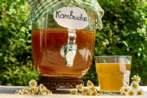 "Photo of kombucha in a glass dispenser on an outside table from ""What Can You Drink During Modified Fasting? Tips, Recipes, and Best Practices"" by Green Smoothie Girl"