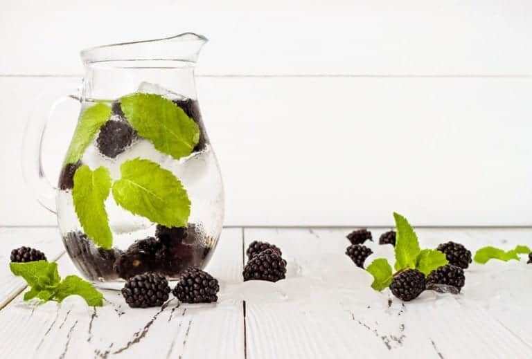 "Photo of ice-cold jug with water, blackberries, and mint leaves inside from ""What can I drink during a modified fast"" by Green Smoothie Girl"