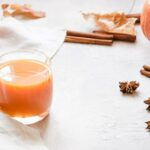 "Photo of warm orange drinks in glasses on white tablecloth from ""Warm Green Smoothies That Are Perfect For Cold Weather"" by Green Smoothie Girl"