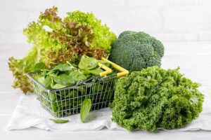 Kale, broccoli, lettuce, baby spinach leaves on white background from
