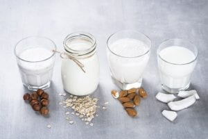 Photo of Coconut, almond, hazelnut, oat homemade milk on stone table from