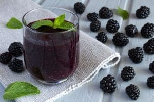 Photo of purple smoothie in glass on grey table runner with surrounding blackberries from
