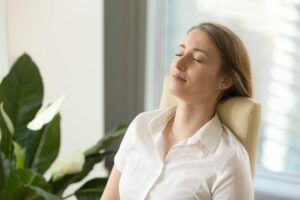 Photo of woman leaning back in chair with eyes closed and calm expression from