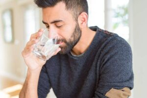 Photo of handsome man drinking clean water from