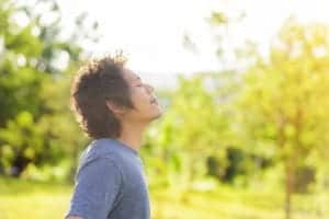 Photo of young Asian man closing eyes and breathing in the air outside from